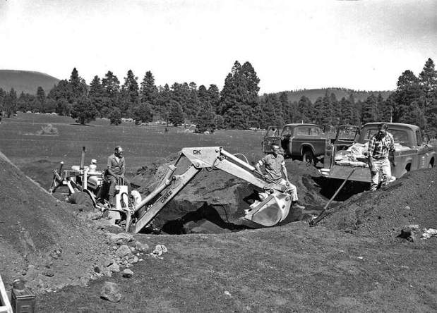 Construction on 27-28 July 1967 of Cinder Lake Crater Field ...Construction on 27-28 July 1967 of Cinder Lake Crater Field # 1 just northeast of Flagstaff, Arizona (a) backhoe digging of 47 holes to precise depths, and in which to bury precisely-measured explosives at each surveyed crater site; red bailey back to camera P447, F106754 USGS Open-File Report 2005-1190, Figure 048a. - ID. Project Apollo (1960-1973) 048a - pap0048a - U.S. Geological Survey - Public domain image